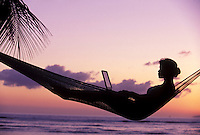 A woman in a hammock uses a laptop at a west Maui sunset.