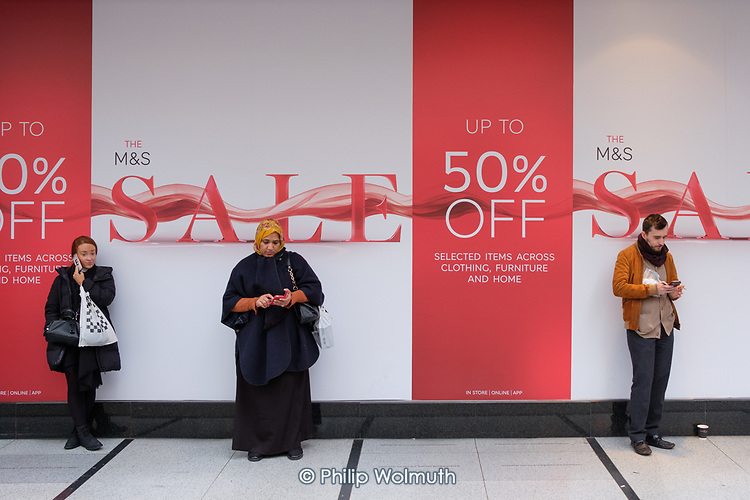 Shoppers with mobile phones wait outside Marks & Spencer store during end of year sale, Oxford Street, London.