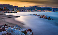 Fine Art Landscape Photograph, of the skyline along Banderas Bay in Puerto Vallarta, Mexico.<br /> <br /> The mix of colors that was cast during the twilight hours blended very well with the golden sunlight and blue ocean waves. The romantic city night lights of Puerto Vallarta and the scenic mountain range makes this a truly beautiful ocean scene.