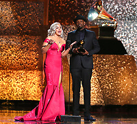 "Joelle James, left, and Larrance Dopson accept the award for best r&b song for ""Boo'd Up"" at the 61st annual Grammy Awards on Sunday, Feb. 10, 2019, in Los Angeles. (Photo by Matt Sayles/Invision/AP)"
