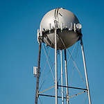 Spherical silver water tank on tower with cell phone antennas, San Ardo, Calif.