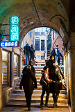 ITALY, Venice. People walking and window shopping in covered alley by St. Mark's Square.