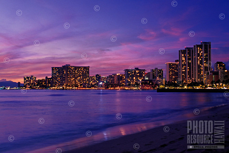 Dazzling Waikiki Beach Skyline at sunset. Hotels glitter against the pastel pinks and purples of the sky creating a mirror reflection in the water.