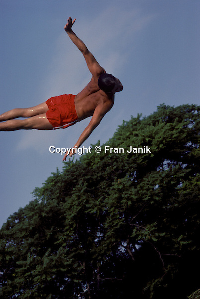 A man in wet red swim trunks with arms extended, dives accross the blue sky, his hand appears to touch the tree top.