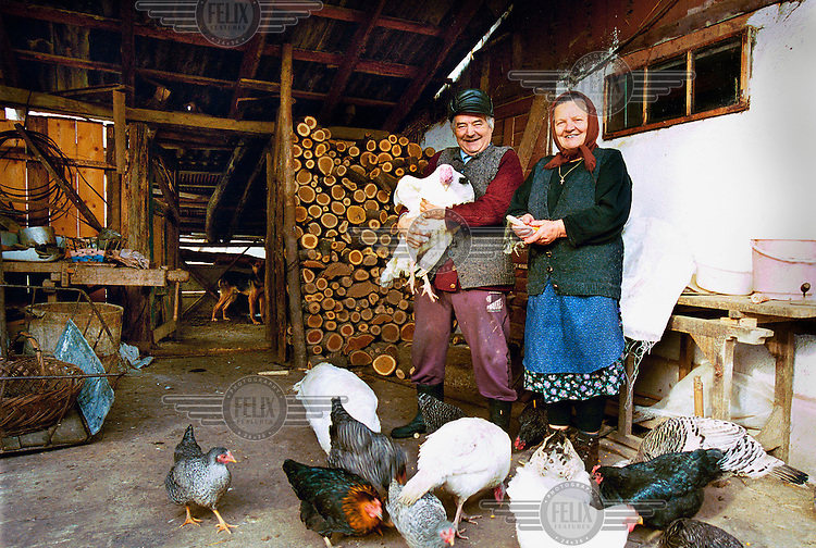 "Ion Furcea (63) with his wife and chickens in their smallholding. He worked as a school director in town, but they returned to his home village after retirement. ""I have no idea how we could hve survived if we didn't have this house with some land. The only people who have enough pension are the politicians and the army. The rest of the population only got some crumbs."""