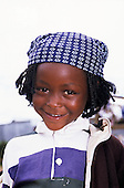 Kilgoris, Kenya. Portrait of a well-dressed smiling girl in a blue headscarf.