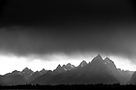 The high peaks of the Tetons glow under a sunset rainstorm in Grand Teton National Park, Jackson Hole, Wyoming.