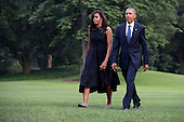 United States President Barack Obama (R) and first lady Michelle Obama walk across the South Lawn after returning to the White House on Marine One July 12, 2016 in Washington, DC. The Obamas were returning from Dallas where they attended a public memorial service for the five Dallas police officers who were killed by a sniper last week during a Black Lives Matter demonstration. <br /> Credit: Chip Somodevilla / Pool via CNP