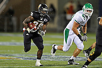 1 September 2011:  FIU running back Darriet Perry (28) runs past North Texas defensive tackle Ryan Boutwell (90) in the first half as the FIU Golden Panthers defeated the University of North Texas, 41-16, at University Park Stadium in Miami, Florida.