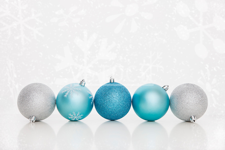 Studio shot of blue and white Christmas ornaments standing in row