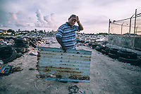 Toni, 38, holds rusted corrugated zinc steel roofing sheet that he found at Ebeye's rubbish dump. He says: 'Sometimes I go here and find useful things for my house'. Children and many unemployed adults often go to the dump in search of any discarded items that they can find use for.