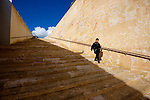 A woman walks the limestone stairs in Valetta, Malta