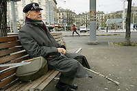 "Switzerland. Geneva. Poverty in Geneva. Henri Delaye is a swiss from the Geneva state and is 63 years old. He is homeless and sits on a bench in the "" Plaine de Plainpalais"". His cap is covered with paper clips. Model Released. © 2005 Didier Ruef"
