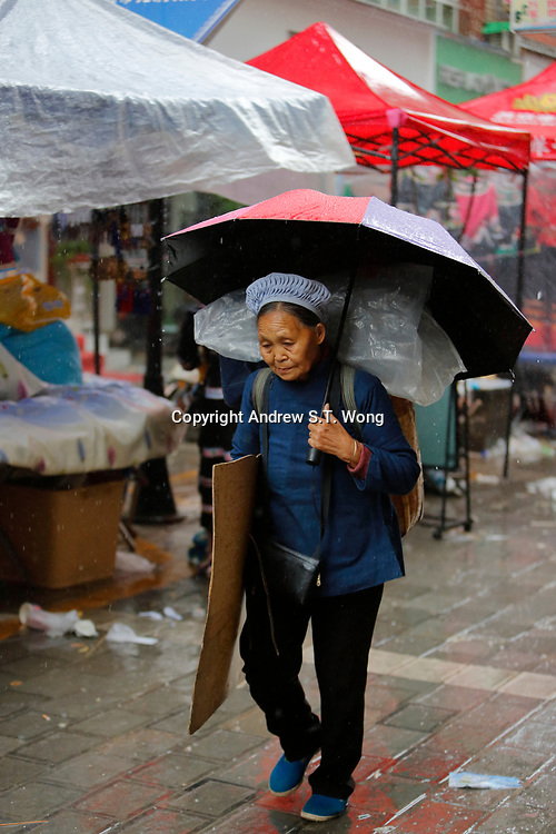 A woman of the ethnic Bouyei Tribe walks in the rain at Wangmo County in China's southwestern Guizhou Province, April 2019.