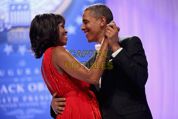 Michelle Obama & Barack Obama.2013 Inauguration Ball, Washinton D.C., USA..January 21st, 2013.half length black suit tuxedo red dress profile holding hands married husband wife dance dancing arm around waist   .CAP/ADM/CNP/CS.©Chip Somodevilla/CNP/AdMedia/Capital Pictures