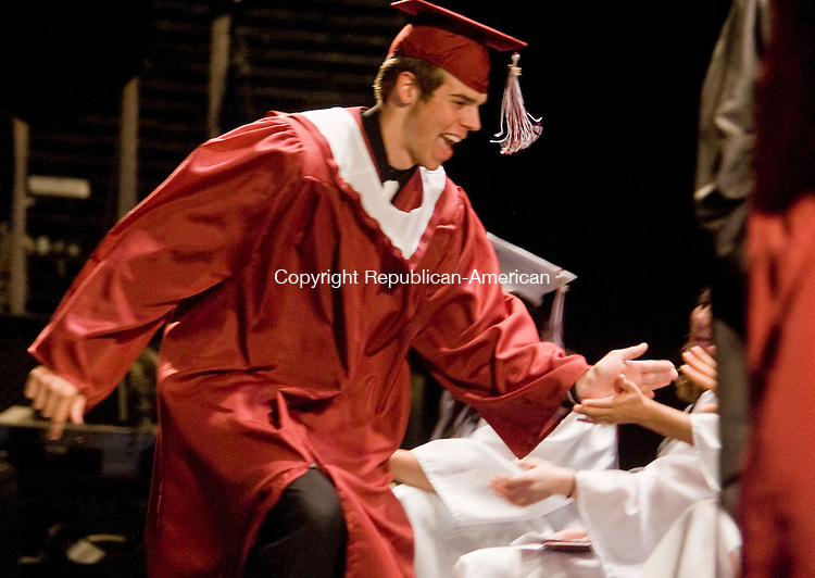 TORRINGTON--15 June 08--061508TJ08 - Alan Rousseau offers a running high-five to classmates sitting on the Warner Theatre stage as he goes to receive his diploma during Torrington High School's graduation on Sunday, June 15, 2008. (T.J. Kirkpatrick/Republican-American)