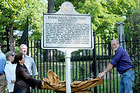 NWA Democrat-Gazette/DAVID GOTTSCHALK Stephanie Wade (left), with the Department of Arkansas Heritage, and Fayetteville Mayor Lioneld Jordan unveil Friday, October 5, 2018, during the dedication ceremony of a new historical marker at the Fayetteville Evergreen Cemetery. The new marker, from the Department of Arkansas Heritage, is the first in Northwest Arkansas and the second in the state to be installed. The cemetery was established in 1847 and added to the National Register of Historic Places in 1997.