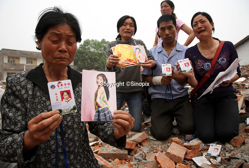 Grieving parents and relatives show the school pass, photo, and awards of their children, who died in a collapsed elementary school in Wufu, Sichuan, China. Over 200 students were claimed to be killed in the quake, all aged 10-13 and overwhelmingly the only child of the family, meanwhile most of the other buildings in Wufu sustained only minor damages..16 May 2008