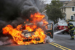 MANASQUAN, NJ — April 1, 2016 — Manasquan firefighter Kevin McCredie squirts water on a 2000 Ford Focus that is fully engulfed in flames about 9:40am on Broad Street, here. The driver of the vehicle, Nancy Trapani, was not injured.  photo by Andrew Mills