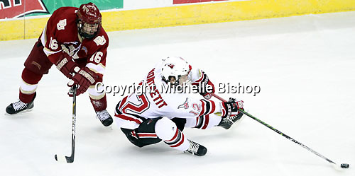 UNO's Brock Montpetit loses his balance after being impeded by     Denver's Anthony Maiani during the first period. Maiani was whistled for hooking on the play. Nebraska-Omaha beat Denver 5-2 Friday night at Qwest Center Omaha. (Photo by Michelle Bishop)