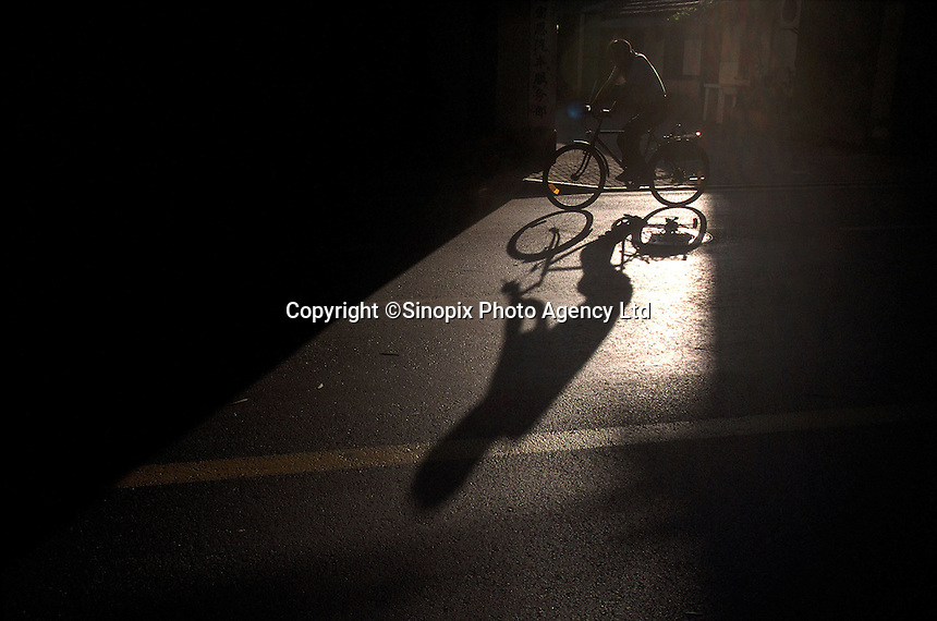 Long shadow of a biker in Shanghai. As car ownership increases, more roads are closed to cyclists, squeezing them from the city center. 11-AUG-01