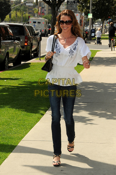SHANNON ELIZABETH.Lloyd Klein Couture Fall 2010 Presentation held at Lloyd Klein House of Couture, Los Angeles, California, USA, 24th  March 2010.. full length white top jeans bag black sandals  shirred waist blue embroidered sunglasses walking  elasticated .CAP/ADM/BP.©Byron Purvis/AdMedia/Capital Pictures.