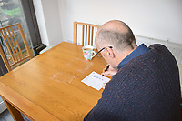 Man completing his postal vote - general election December 2019 UK. MR