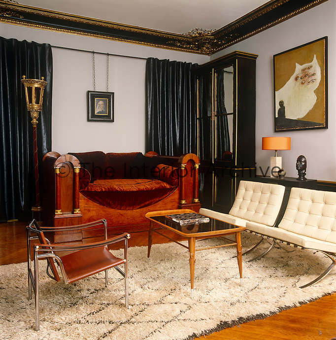 The dove grey on the walls of the living room of a Paris apartment complements the black and gold mouldings as well as the warm deep brown velvet covering the lit a la Polonaise once slept in by Napoleon