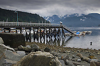 Wooden  jetty at Deep Cove Bay with clouds above the mountains over Mount Seymour provincial park. Deep Cove, Burrard Inlet, Vancouver, British Columbia, Canada.