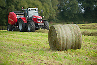 Round bale of silage in a field, Cheshire with a round baler in the background.