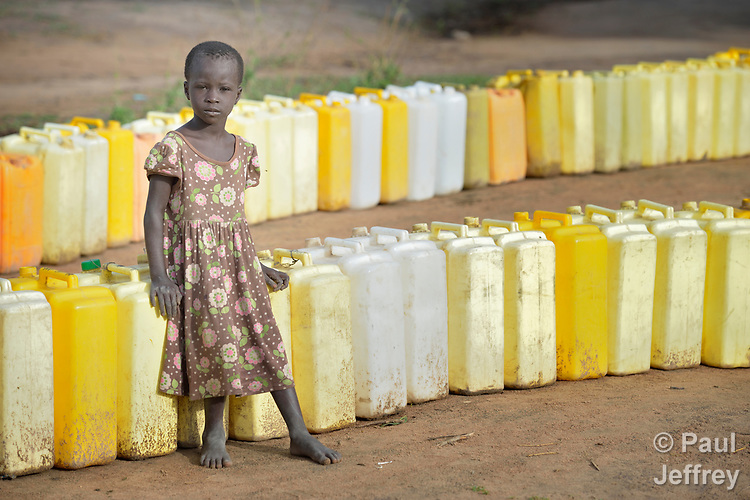 Feba Awanyna, 5, keeps watch on a row of jerry cans before dawn in the Rhino Refugee Camp in northern Uganda. As of April 2017, the camp held almost 87,000 refugees from South Sudan, and more people were arriving daily. About 1.8 million people have fled South Sudan since civil war broke out there at the end of 2013. About 900,000 have sought refuge in Uganda. <br /> <br /> Because water pumps in the camp are solar-powered, water can only be obtained during daylight hours. Refugees will therefore line up their jerry cans overnight in order to be among the first to get water in the morning.<br /> <br /> The Global Health Program of the United Methodist Church has supported work to improve access to safe drinking water in the camp.