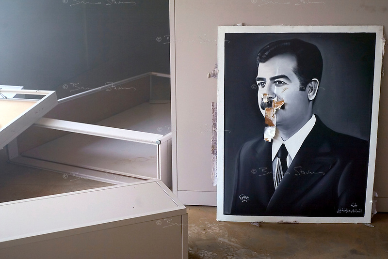 """Baghdad, Iraq, April 13, 2003.A vandalized canvas in the painting section of the """"Triumphant Leader Museum"""", entirely dedicated to the glory of Saddam Hussein, set on fire today."""