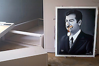 "Baghdad, Iraq, April 13, 2003.A vandalized canvas in the painting section of the ""Triumphant Leader Museum"", entirely dedicated to the glory of Saddam Hussein, set on fire today."