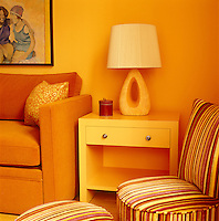In the living room of a New York apartment the walls glow a vivid orange, continued in the upholstery of the sofa and in the stripes of a chair and matching pouffe