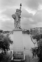 "France. Ile-de-france Department. Paris. Original Statue of Liberty on the Île aux Cygnes near the Grenelle Bridge. Given to the city  and inaugurated on July 4, 1889, it looks southwest, downriver along the Seine. Its tablet bears two dates: ""IV JUILLET 1776"" (July 4, 1776: the United States Declaration of Independence) like the New York statue, and ""XIV JUILLET 1789"" (July 14, 1789: the storming of the Bastille). Men jogging.  10.06.10 © 2010 Didier Ruef"