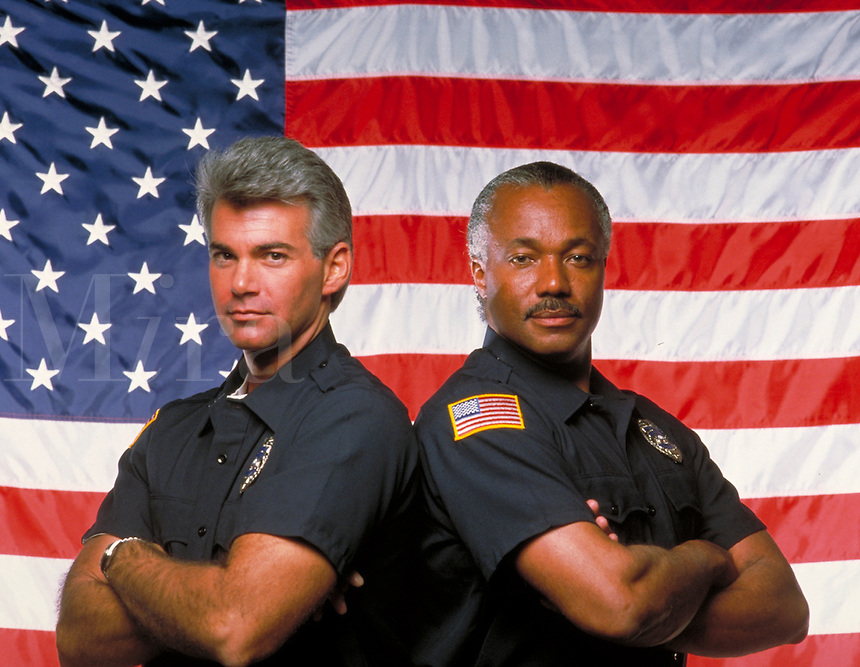Two Uniformed, White, African American policemen standing in front of United States flag. Black man, occupations, law enforcement, uniform clothing, policeman, confident, arms crossed, pleasant, police. R. Williams, R. Bradbury M.R. # r-8.