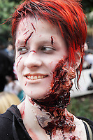 Headshot of red hair woman from the zombie walk in prague may 2014, having a make up wound on her neck.