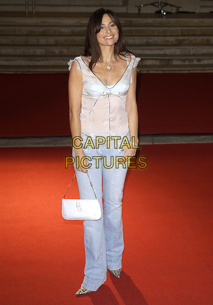 MINNIE DRIVER.Red Carpet Arrivals at the Brit Awards 2005,.Earls Court 2, London, February 9th 2005..full length straight hair  white top pale stonewashed jeans bag.Ref: PL.www.capitalpictures.com.sales@capitalpictures.com.©Capital Pictures.