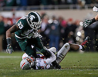 Ohio State Buckeyes cornerback Eli Apple (13) tackles Michigan State Spartans running back Jeremy Langford (33) during the third quarter of the NCAA football game at Spartan Stadium in East Lansing, Michigan on Nov. 8, 2014. (Adam Cairns / The Columbus Dispatch)