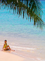 Woman relaxing on white sand beach under palm leaf