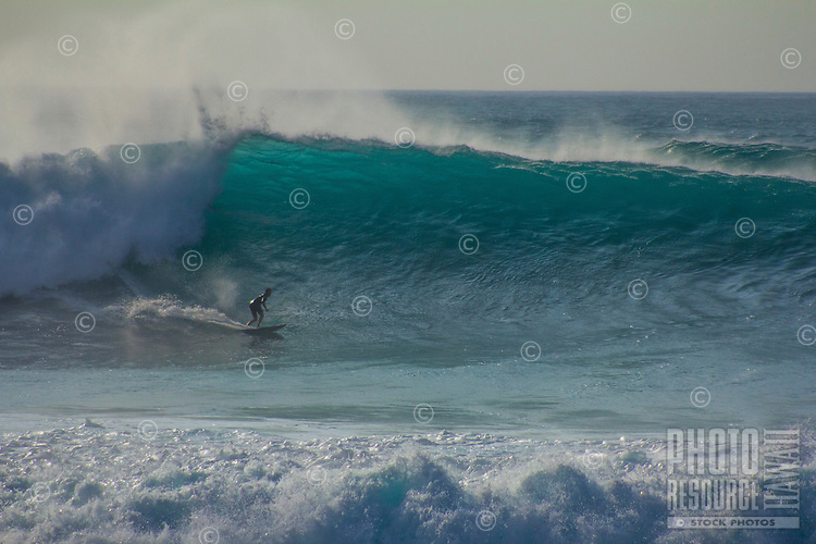 A surfer turns off the bottom of a large wave at Pipeline, North Shore, O'ahu.