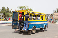 Senegal, Saint Louis.  Young Men often stand on the running board on the rear of the local minibuses providing urban transport.  This one is about to pass over the  Pont Faidherbe Bridge over the River Senegal.  Built 1897.