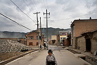 A woman walks along the streets of Xiahe, Gansu, China.  Xiahe, home of the Labrang Monastery, is an important site for Tibetan Buddhists.  The population of the town is divided between ethnic Tibetans, Muslims, and Han Chinese.