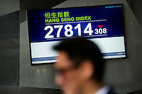 HONG KONG - MAY 05: A man walks pass a stock exchange board displaying the Hong Kong index (Hang Seng index) in Central business district, on May 5, in Hong Kong. (Photo by Lucas Schifres/Pictobank)