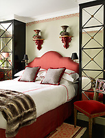 In the guest room, custom-made cabinets with mirror fronts stand either side of the bed, which has a rich red upholstered headboard. The 18th-century chair is Italian and the 19th-century vases are French; the walls are painted in Farrow & Ball's French Gray, trimmed with a hand painted Chinese key pattern.