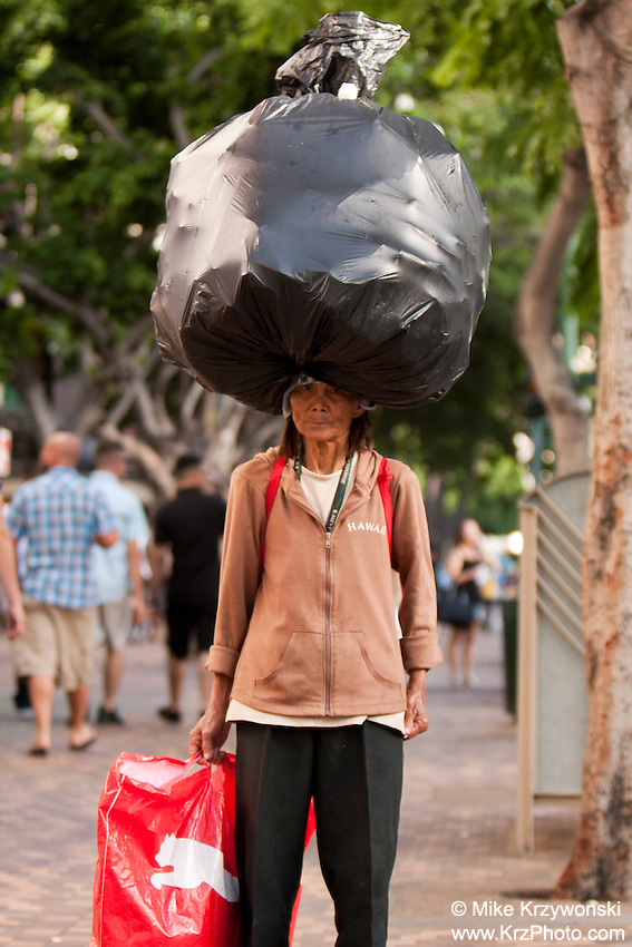 Elderly Asian woman carrying large load on top of her head in Waikiki, Honolulu, Oahu, Hawaii
