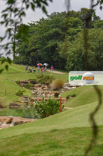A long view of players making their way down 4 near the waterfalls during Rd 2 of the Asia-Pacific Amateur Championship, Sentosa Golf Club, Singapore. 10/5/2018.<br /> Picture: Golffile | Ken Murray<br /> <br /> <br /> All photo usage must carry mandatory copyright credit (© Golffile | Ken Murray)