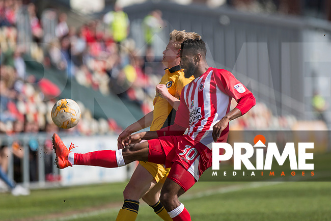 Janoi Donacien of Accrington Stanley clears from Alex Samuel of Newport County during the Sky Bet League 2 match between Newport County and Accrington Stanley at Rodney Parade, Newport, Wales on 22 April 2017. Photo by Mark  Hawkins.