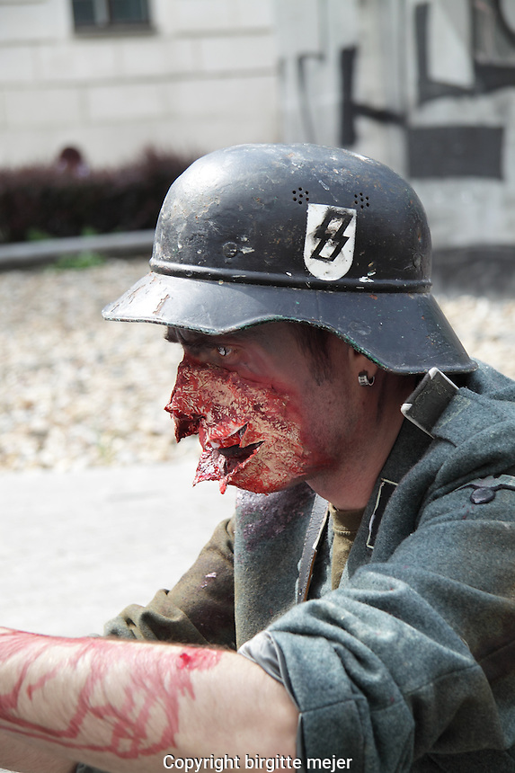 Male participant in the prague zombie walk may 2014 photographed in profile wearing a soldiers uniform and a soldiers helmet.