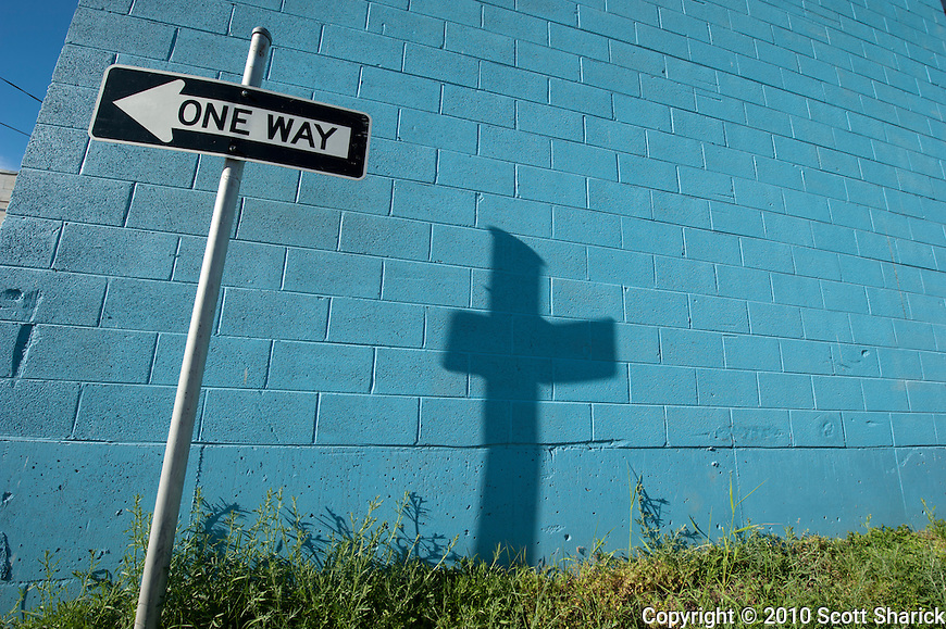 A 'One Way' sign creates a shadow in the shape of a cross against a cinder block wall that has been painted blue. Missoula Photographer, Missoula Photographers, Montana Pictures, Montana Photos, Photos of Montana